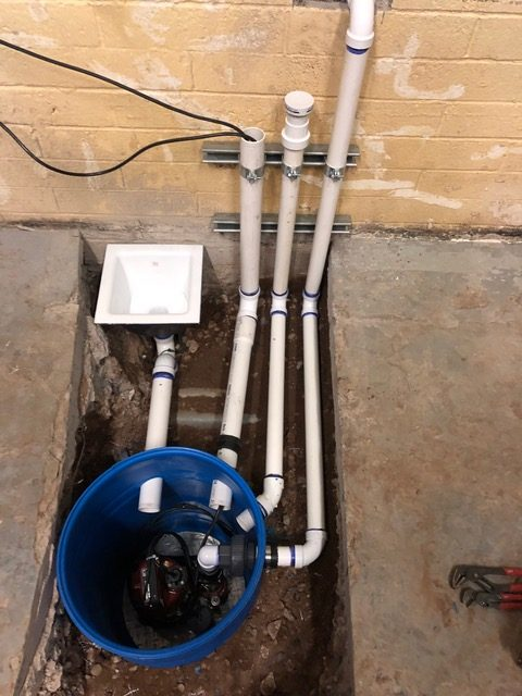 Sump pit with drain lines coming into it, floor sink for future use. Vent line and ejector line run along wall to sewer main outside.
